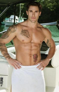 Buffed hunk wrapped in towel with snake tattoo coiled on his right arm and other tats