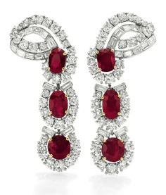 A PAIR OF RUBY AND DIAMOND EAR PENDANTS, BY CARTIER  Each set with a line of three oval and cushion-cut rubies, each within a circular and baguette-cut diamond surround, to the circular and baguette-cut diamond scrolling surmount, mounted in platinum and 18k gold, with French assay marks and maker's marks $782,500.00