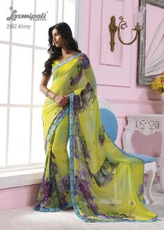 This parrot green georgette material saree with sky blue color border & with multi color flowers prints.