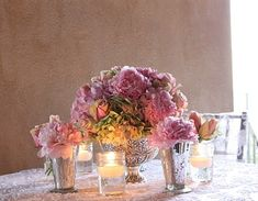 Some tables would also feature low arrangements of roses, peonies, and hydrangeas in silver urns with julip cups as bud vases