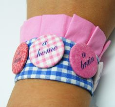 Badges on a fabric cuff bracelet.