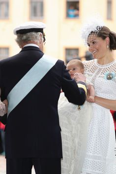 King Carl XVI Gustaf strokes the cheek of his grandson Prince Oscar. The little prince was the star of his christening (27 May 2016). Seen here in the arms of his mother Crown Princess Victoria.