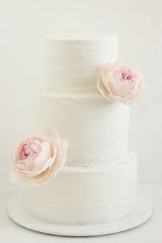 Simple, white buttercream wedding cake with light pink peonies made of sugar.