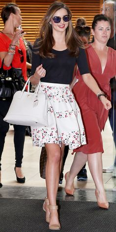 Miranda Kerr got around Sydney in a black top, floral skirt, leather Prada tote and ankle-strap heels.