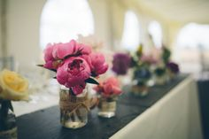Glass vases filled with vibrant posies of garden flowers sat on slate