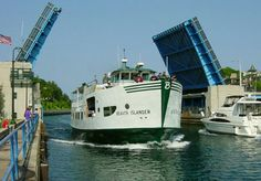 The former ferry, Beaver Islander, leaving Charlevoix.  The bridge must be raised for it while traffic waits.