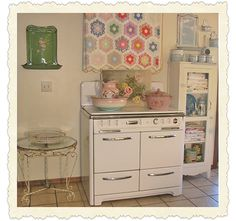 cute cottage kitchen - love the quilt and vintage stove - featured on http://theoldpaintedcottage.com/pages/cottagemonth_enter.htm