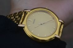 a close up of a gold watch on a persons hand