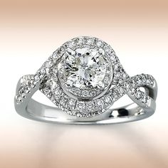14K White Gold 1 1/4 Carat t.w. Diamond Engagement Ring  A scintillating round diamond rests in the center of this dramatic ring for her. Diamond-decorated twists of 14K white gold engulf the center stone in breathtaking brilliance. 1 1/4 carats total weight