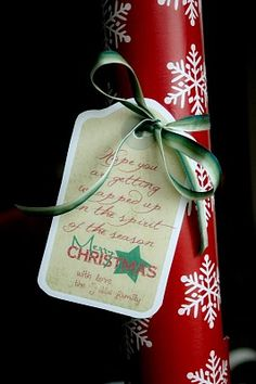 "Simply a roll of Christmas wrapping paper and a tag.    The tag says, ""We hope you are getting wrapped up in the spirit of the season. Merry Christmas! with love, the _____ family"""