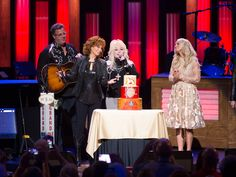 """Reba McEntire celebrated the 40th anniversary of her Grand Ole Opry debut with two shows last night (Sept. 22)—and two surprise guests: Dolly Parton and Carrie Underwood. If was a full circle moment for Reba, as she was upstaged by Dolly during her Opry debut on Sept. 17, 1977. """"First time I e"""