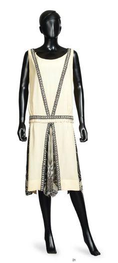 JEAN PATOU, 1927 Black And White ROBE DU SOIR en crêpe soie ivoire agrémentée de galons incrustés noirs rebrodés de perles de verre et de strass figurant un décor géométrique, décolleté rond sur échancrure en pointe au dos, taille basse soulignée d'une ceinture, jupe à quilles, chacune composée de trois lès rebrodés d'un motif végétal stylisé à finitions festonnées.