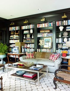Library of my dreams:  dark bookshelves, leopard print on back of sofa, ikat (or suzani) pillows and a beni ourain on the floor!