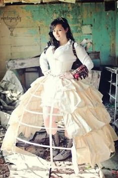 From the Steampunk Fashion Guide to Skirts & Dresses: Cage Skirts - This is an example of a woman wearing a long hoop skirt/hoop petticoat with half open overskirt in a showgirl style