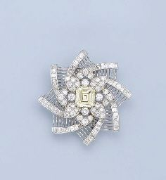 A YELLOW DIAMOND AND DIAMOND BROOCH. The central rectangular-shaped 4.10 carat…