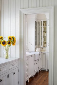 Bright Martha's Vineyard kitchen with beadboard, marble countertops, and a deep farmhouse sink.