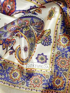 Length: 34 Inches; Width: 34 Inches  Description  This is a very luxury Sunkyung SA designer scarf. This large square paisley scarf combines rich colors of royal blue, orange, yellow and red on a beige background. The paisley floral pattern is very pronounced and looks jubilant and vibrant. The scarf feels like silk but I think it is polyester. The scarf is in mint condition and will make a beautiful gift. The scarf can be used as a shawl, head scarf and neck wrap. It will add lots of… Multi Coloured Scarves, Paisley Scarves, Designer Scarves, Beige Background, Rich Colors, Neck Wrap, Square Scarf, Orange Yellow, Vera Bradley Backpack