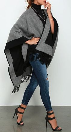 Automne hiver. Poncho noir et gris, sous pull noir, jean destroy bleu, escarpins noirs