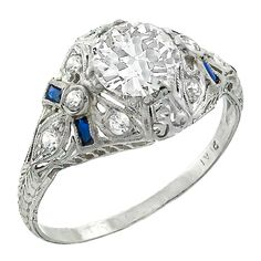 Art Deco 1.09 Carat Old European Cut Diamond Sapphire Ring. Handcrafted from the Art Deco era, this platinum ring centers a sparkling GIA certified old European cut diamond that weighs 1.09ct. and is graded H color with SI2 clarity. The center stone is accentuated by sparkling round cut diamonds and vivid blue faceted cut sapphire accents.