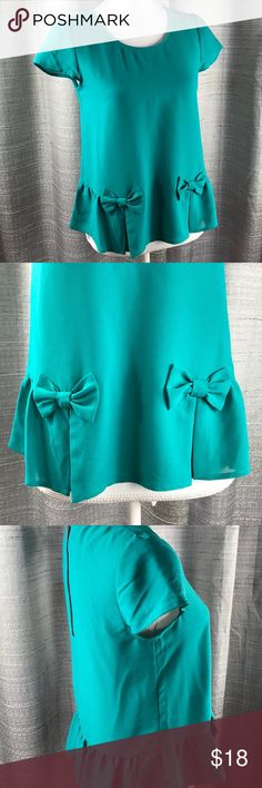 Teal Peplum Eric + Lani Blouse Teal cap sleeved peplum top with bow details around the bottom. Black working zipper on back. Semi sheer material. eric + lani Tops Blouses