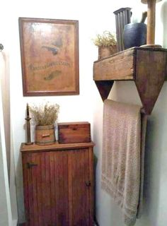 Old wooden toolbox turned upside down and attached to wall - doubles as a shelf and towel storage. Clever!