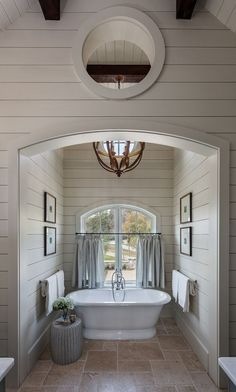 Arch bath nook with shiplap paneling, arched window, exposed beams, orb pendant light and framed art. Wright Design. Inspiro 8 Studios Photography.