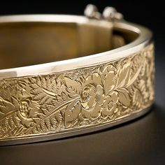 Victorian engraved bangle bracelet. Sublime floral motif hand engraving adorns the top half of this extra-sweet and lovely, 1/2 inch wide, hinged bangle bracelet, finely crafted in sturdy 9 karat yellow gold, by way of nineteenth-century great Britain. Lang Antiques.