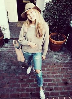 Gigi Hadid wearing fedora hat, brown oversized jumper, ripped boyfriend jeans paired with white converse