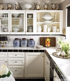 Designers and owners Craig Schumacher and Philip Kirk avoided an extensive kitchen remodel by painting existing cabinets Benjamin Moore Brilliant White and installing inexpensive black and white tile on counters and backsplashes. An extensive iron stone collection overflows from shelves to walls. Schumacher and Kirk collected enough quarters in the three ginger gars to buy a new flat-screen TV.   - HouseBeautiful.com