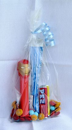 Alternate party favor for neighbor cake & ice cream (older kids) party.    Iron Man 2012 Pez dispenser & lemon and strawberry PEZ candies, gold personalized M's, standard red M's, light blue Sixlets, light blue curling ribbon.