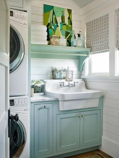 Eye catching turquoise blue laundry room cabinets topped with white marble countertops holding an apron sink accented with a polished nickel faucet is sat against white shiplap walls under a turquoise mounted shelf holding glass storage jars and green abstract canvas art piece.