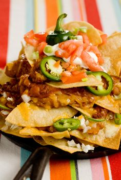 """The Deen Brothers' Lighter Macho Nachos ♨ 6 (6"""") fat-free flour tortillas, ½ cup fat-free refried beans, 1 small onion, ½ cup reduced-fat shredded MontereyJack cheese, 1 sliced jalapeno, 15-oz) can vegetarian chili with beans, ¾ cup fat-free sour cream, 1 diced tomato, ¼ cup chopped scallions ♨ 157 Calories, 11g Protein; 7g Fat, 15g Carbs, 6g Fiber"""
