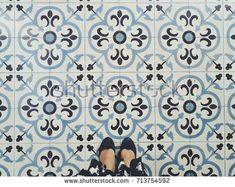 Lady wearing dress that selfie of feet with black shoes on art pattern tiles floor. Top view.