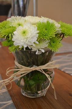 Lime green and white flowers in a vase tied with a jute string as a centerpiece on the tables.