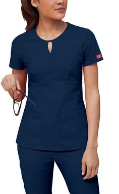 A mock wrap top features a key hold neckline, an empire waist, bust darts, patch pockets and side vents. Center back length: 25 Fabric: Cotton Poplin. Dental Uniforms, Work Uniforms, Healthcare Uniforms, Spa Uniform, Scrubs Uniform, Stylish Scrubs, Scrubs Outfit, Cute Scrubs, Iranian Women Fashion