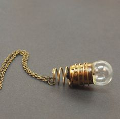 """Steampunk Jewelry- Brass Industrial Light Bulb Necklace This steampunk necklace is made from an old light bulb and a salvaged vintage brass coil. The light bulb pendant is hung from a 20"""" antiqued ..."""
