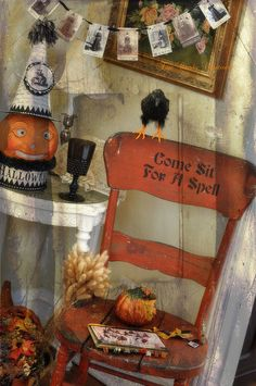 vintage or antique Halloween style decorations- orange painted chair, raven, jack o lantern, and photo garland