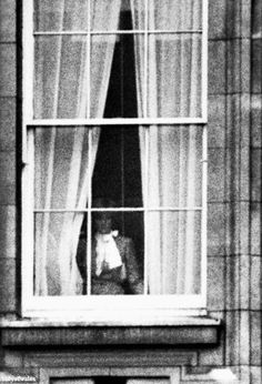 Diana peering out a Buckingham Palace window on the day of her engagement. February, 1981