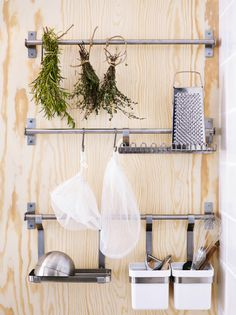 Three stainless steel IKEA rails with hooks and containers holiding different kitchen tools.