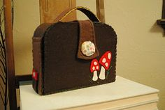 Felt Doll House Suitcase. When you open up there are pockets for felt dolls and all the furniture. There is a mat that rolls out and has rooms of house appliqued on it. Very cute! She sells a kit or the pattern to make your own.