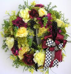 """The wreath is embellished with lots of greenery, beautiful yellow Peonies, wine color Dahlias, apple green Dahlias , yellow Roses, and lime green Hydrangeas. The wreath is accented with four small clusters of wine grapes and three clusters of green grapes, and a black Eiffel Tower in the middle . I finish the wreath with a high end black/white check and wine color Ribbon Bow.  The wreath measures from tip to tip at 23"""" (L) x 23"""" (W) x 7""""(D)."""