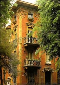 saffron colored exterior, elaborat architecture\al details Balconies, Bologna, Italy