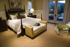 This elegant bedroom places an open back couch at the center, with white cushions and bedding matching the two-tone wall coloring.