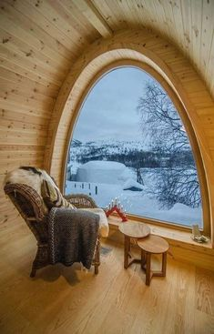 chair in front of half circle window in wood cabin looking out into snow covered trees