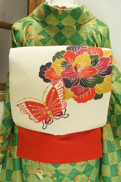 象牙色地に、若草緑、山吹色、珊瑚紅色、橙色、茄子紺など華やかで詩情豊かな彩りで染め出された牡丹のような大輪の花に遊ぶ蝶々が美しい紅型調の名古屋帯です。