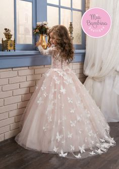 The Kansas flower girl dress charms the heart with beautiful lace overlayed bodice with long sleeves and a multi-layered tulle skirt. Unique butterflies design adorns the overskirt detail extending fr