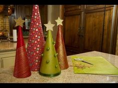 Make your own holiday decorations - Christmas trees made from wrapping paper!    Jessie Jane of  Lilyshop (http://www.lilyshop.com) shares a fun and festive craft project that is sure to brighten your home for the holiday season!    ::Subscribe to the ModernMom Channel::  http://www.youtube.com/subscription_center?add_user=modernmom    ::ModernMom on F...