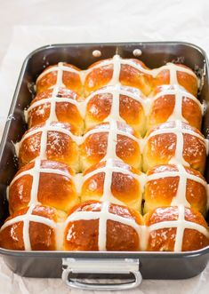 Traditional Hot Cross Buns with a cream cheese icing, brushed with a sweet syrup and filled with juicy raisins. Perfect for your Easter brunch.