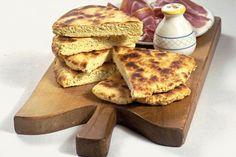 """La """"torta al testo"""" è conosciuta sin dall'antichità. Tipica della tradizione perugina, è una schiacciata di farina, acqua, olio extravergine di oliva, un pizzico di sale e, se la si vuole far alzare un po', una punta di bicarbonato o di lievito di birra. La torta deve il suo nome al """"testo"""", la pietra piatta refrattaria resa rovente dal fuoco ed utilizzata in origine per la sua cottura, ma in Umbria la chiamano anche """"crescia"""", """"torta del panaro"""" o """"pizza sotto il fuoco"""" (Terni).   Elaborata…"""