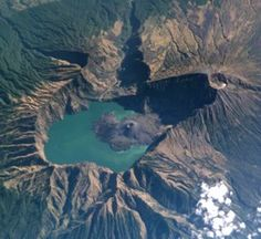 This spectacular NASA Space Shuttle image with north to the top taken in 2002 shows the 6 x 8.5 km wide Segara Anak caldera, elongated E-W, with a crescent-shaped caldera lake. The post-caldera cone of Baru Jani (New Mountain) has been the source of lava flows that have entered the lake. The 3276-m-high summit of Rinjani (right) is cut by a crater that postdates caldera formation.